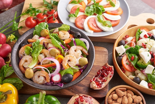 Healthy salad plate. fresh seafood recipe. grilled shrimps and fresh vegetable salad. healthy food. flat lay. top view. shrimp salad with tomato, olives and almond nuts. mix vegetables.