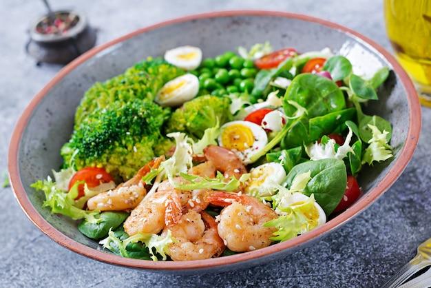 Healthy salad plate.  grilled shrimps and fresh vegetable salad, egg and broccoli.