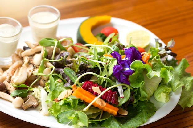 Healthy salad on a plate placed on a wooden table.