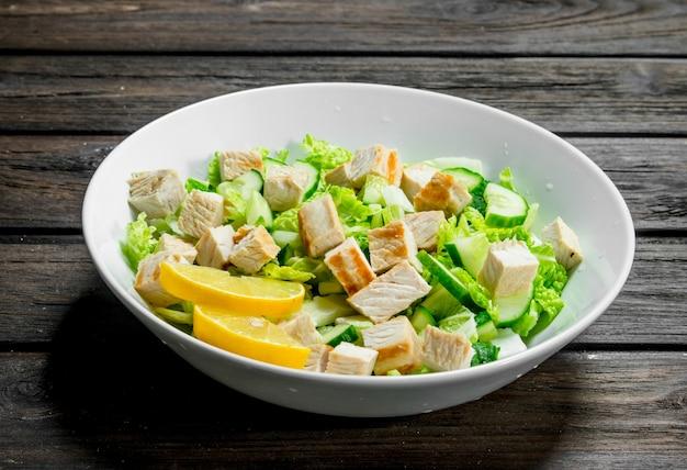 Здоровый салат. салат с огурцами, курицей и пекинской капустой залит лимонным соком. на деревянном фоне.