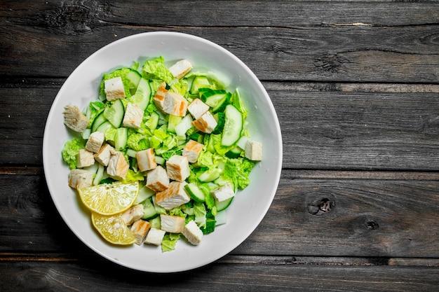Здоровый салат. салат с огурцами, курицей и пекинской капустой залит лимонным соком. на деревянном.