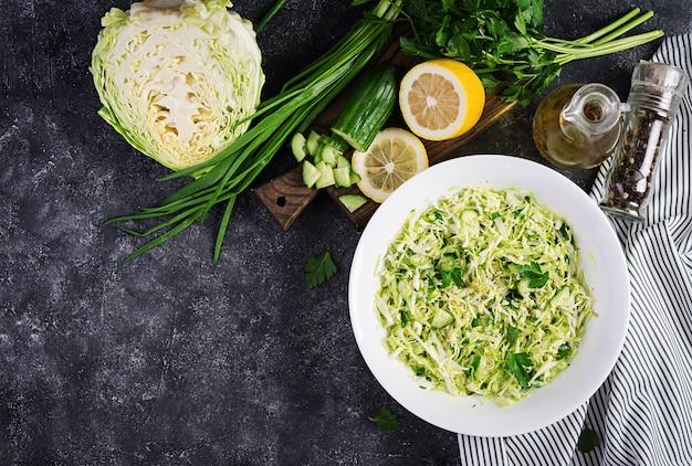 Полезный салат весенний веганский салат с капустой, огурцом, зеленым луком и петрушкой на темном столе. вид сверху