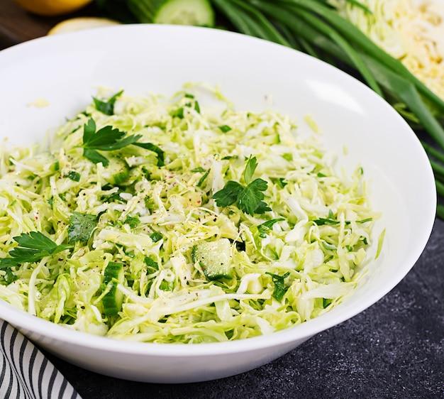Полезный салат весенний веганский салат с капустой, огурцом, зеленым луком и петрушкой на темном столе.