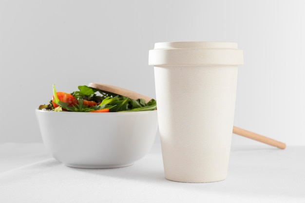 Healthy salad in white bowl with paper cup of coffee
