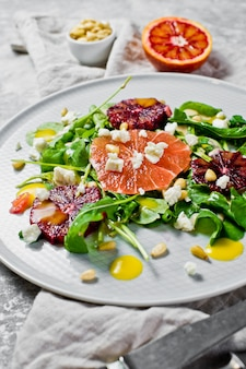 Healthy salad with arugula, grapefruit, red oranges, nuts and tofu cheese.