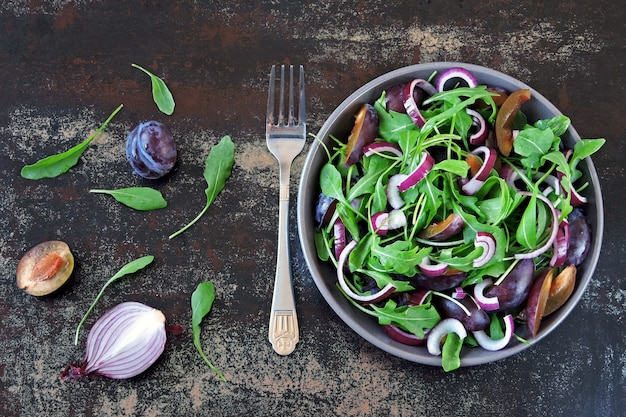 Healthy salad with arugula, plum and blue onions in a bowl on a stylish shabby background