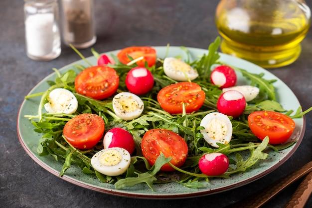 ルッコラ、ウズラeqqs、チェリートマトのヘルシーサラダ。ダイエット食品のコンセプト。