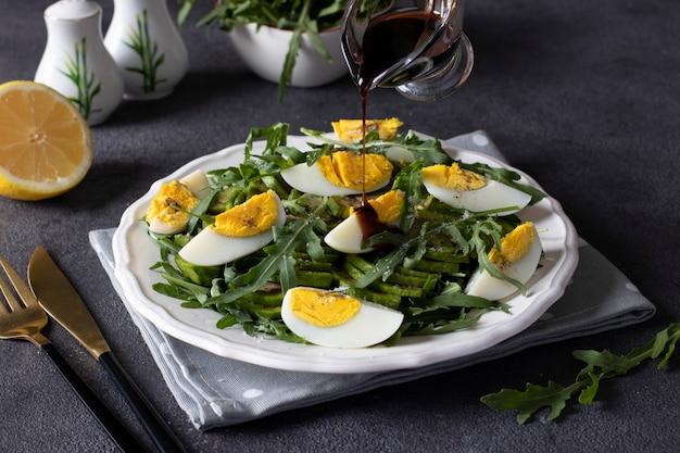 Здоровый салат с авокадо, рукколой и яйцами на белой тарелке на темно-сером фоне. повар поливает салат бальзамическим соусом.