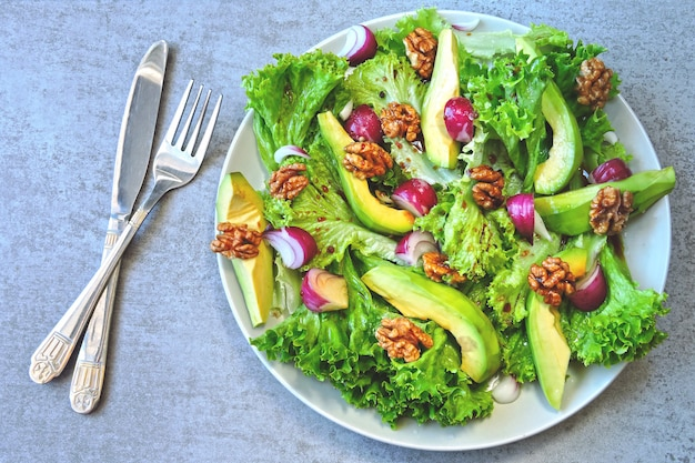 Healthy salad with avocado, blue onion and walnuts. keto salad superfoods