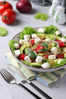 灰色の背景、クローズアップ、垂直形式でアボカド、トマト、フェタチーズ、赤玉ねぎのヘルシーサラダ