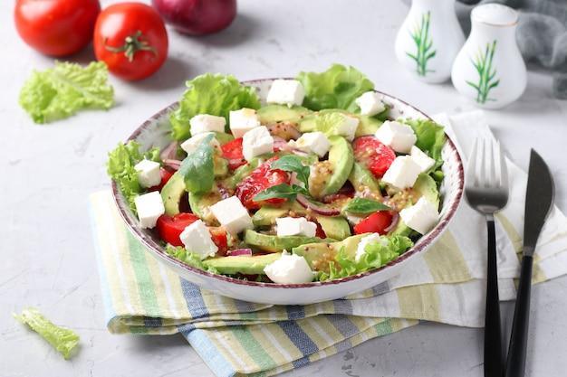 Здоровый салат с авокадо, помидорами, фетой и красным луком на сером фоне, день здорового питания