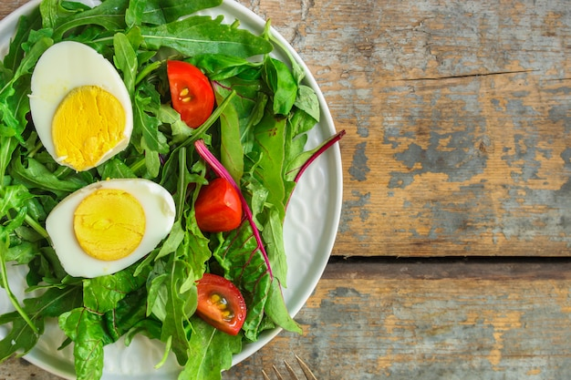 Healthy salad with boiled egg, mix lettuce leaves, tomatoo, appetizer, snack