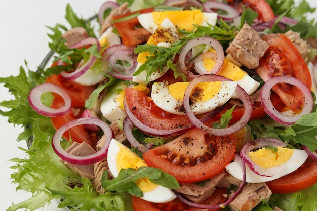 Healthy salad with canned tuna, tomatoes, eggs, arugula, red onions and microgreens, closeup