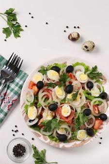 缶詰のマグロ、トマト、ウズラの卵、ブラックオリーブ、白ねぎ、白い表面に有機レタスを添えたヘルシーサラダ、上面図、垂直フォーマット