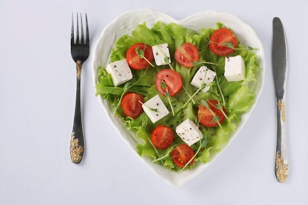 흰색 테이블에 하트 모양의 접시에 체리 토마토, 죽은 태아와 완두콩 마이크로 그린, 건강한 식생활의 날, 상위 뷰와 건강 샐러드