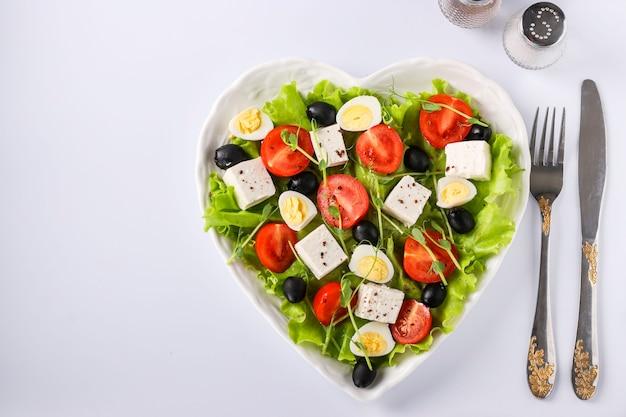 白い表面のハート型プレートにチェリートマト、フェタチーズ、ウズラの卵、オリーブ、マイクログリーンのヘルシーサラダ、健康的な食事の日、上面図、コピースペース