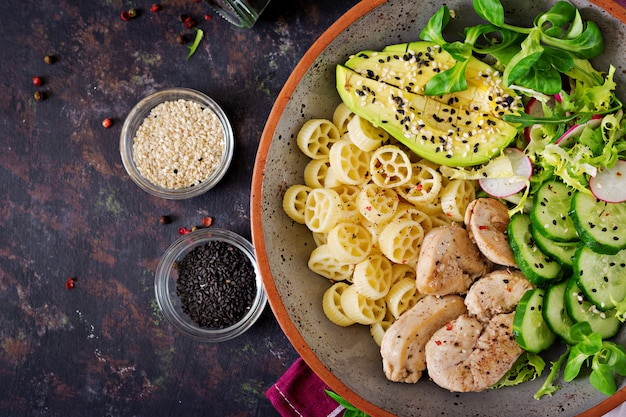 Healthy salad with chicken, avocado, cucumber, lettuce, radish  and pasta on dark table. proper nutrition. dietary menu. dinner. flat lay. top view