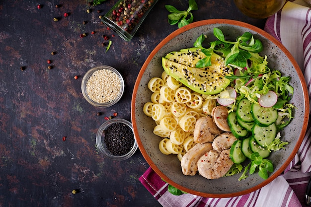 Healthy salad with chicken, avocado, cucumber, lettuce, radish  and pasta on dark