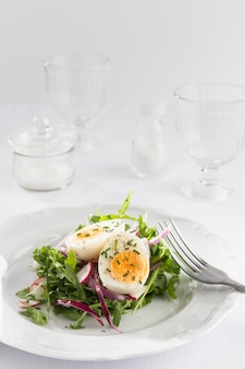 Healthy salad with egg on a white plate assortment