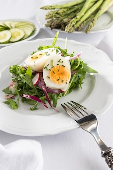 Healthy salad with egg on a white plate composition