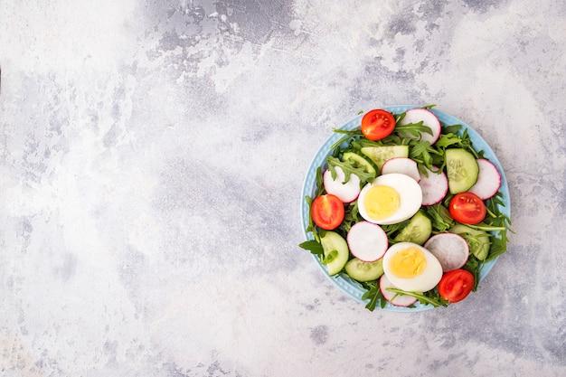 Здоровый салат с яйцами и свежими овощами на тарелке. вид сверху.