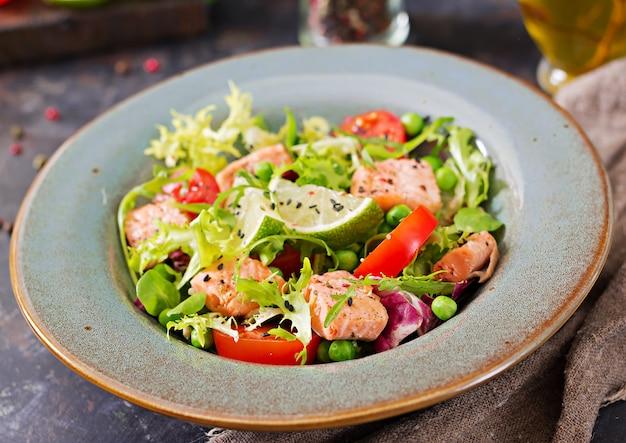 魚のヘルシーサラダ。焼きsal、トマト、ライム、レタス。健康的な夕食。