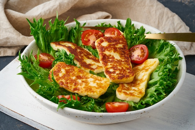Healthy salad with fried halloumi and tomatoes, closeup, keto ketogenic diet