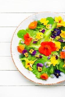 녹색 양상추와 식용 꽃을 곁들인 건강 샐러드입니다. 접시에 꽃이 든 그린 샐러드