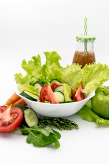 Healthy salad with juice against white background
