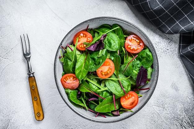 샐러드 그릇에 망골드, 스위스 근대, 시금치, 아루굴라 잎이 섞인 건강한 샐러드. 흰 바탕. 평면도.