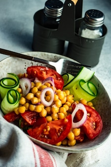 Healthy salad with organic vegetables and chickpea served in a bowl