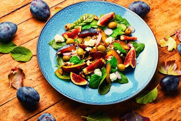 プラム、イチジク、オリーブ、フェタチーズのヘルシーサラダ。フルーツとハーブの秋のサラダ。