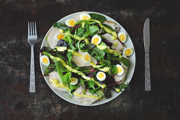 Healthy salad with quail eggs, salad mix and chicken breast. keto diet.