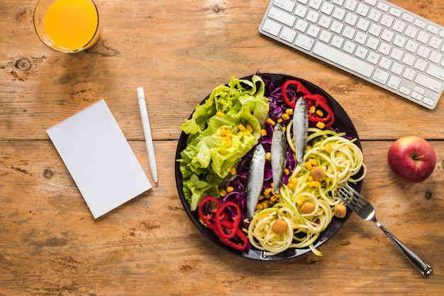 Healthy salad with raw fish arranged in plate; juice; apple; keyboard and notepad; pen on wooden desk