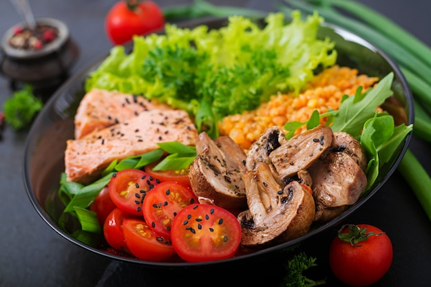 Healthy salad with salmon, tomatoes, mushrooms, lettuce and lentil on dark