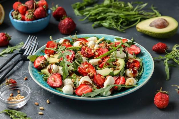 Полезный салат с клубникой, авокадо, рукколой и моцареллой, заправленный оливковым маслом и бальзамической заправкой в синей тарелке на черном