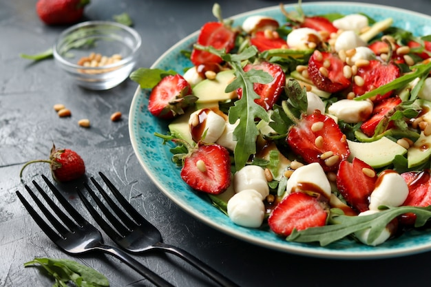 Healthy salad with strawberries, avocado, arugula and mozzarella, dressed with olive oil and balsamic dressing on dark