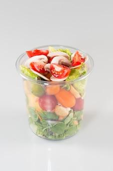 플라스틱 컵에 담긴 건강 샐러드 점심을 먹으십시오. 채식 음식 개념
