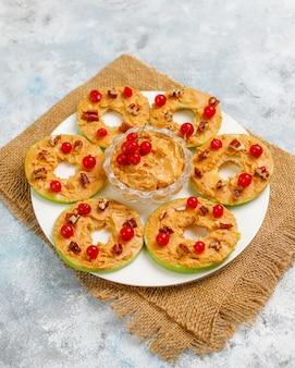 Здоровый бутерброд. зеленые яблоки с ореховым маслом и красной смородиной и орехами пекан на сером бетоне, вид сверху