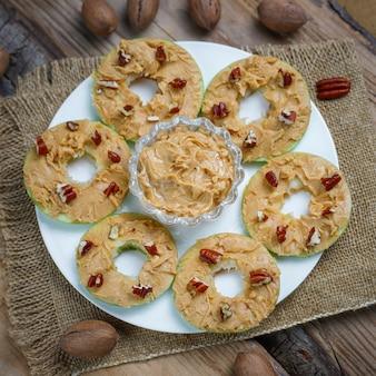Здоровый бутерброд. зеленое яблоко с ореховым маслом и красной смородиной и орехами пекан на деревенском, вид сверху