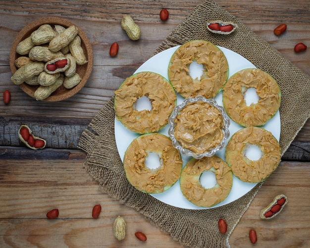 Healthy sandwich. green apple rounds with peanut butter and red currant and pecan nuts on rustic, top view