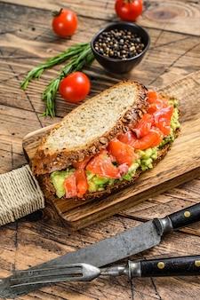 Полезный бутерброд с авокадо и лососем. деревянный фон. вид сверху.