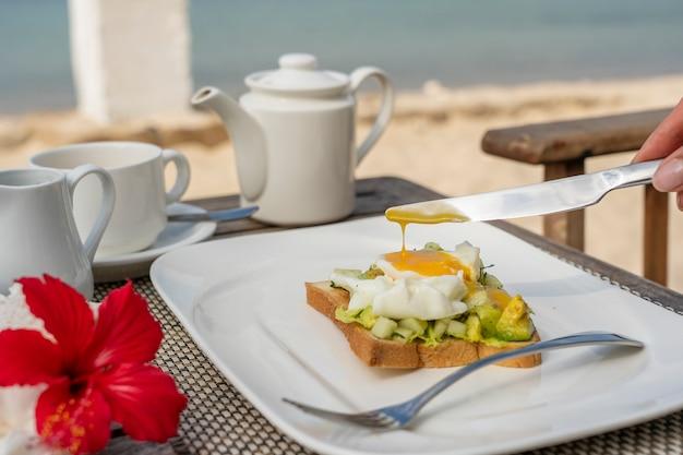 海の近くのビーチで健康的な朝食のためのテーブルにアボカド、キュウリ、ポーチドエッグのヘルシーなサンドイッチ。食品と朝食のコンセプトです。