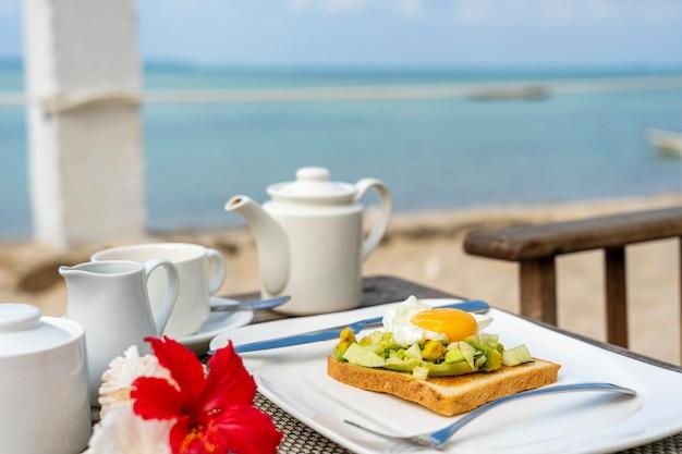 海の近くのビーチで健康的な朝食のためのテーブルにアボカド、キュウリ、ポーチドエッグのヘルシーサンドイッチ