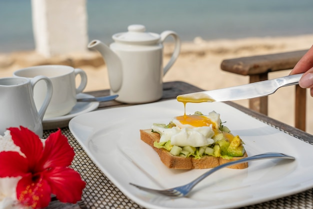 Healthy sandwich with avocado, cucumber and poached eggs on table for healthy breakfast on the beach near sea. food and breakfast concept.