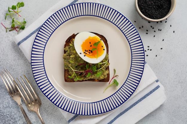 아침 식사로 서빙 접시에 토스트에 아보카도, 계란, 마이크로그린을 곁들인 건강한 샌드위치. 건강한 영양식이 개념. 평면도.