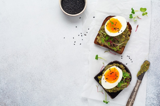 아침 식사로 서빙 접시에 토스트에 아보카도, 계란, 마이크로그린을 곁들인 건강한 샌드위치. 건강한 영양식이 개념. 평면도