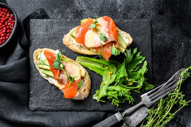 Healthy sandwich with avocado and salmon. spinach and arugula salad. black background. top view.