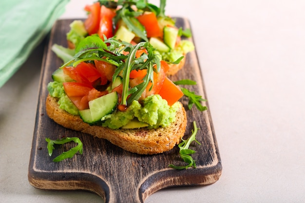 Healthy sandwich with avocado and vegetable topping: tomato, cucumber