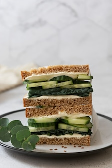 Healthy sandwich with cucumber and kale leaves.